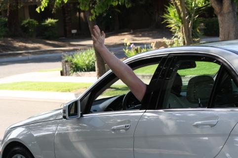 in car waving